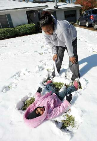 Lisa Brackett helps her daughter Jeleesia Brackett, 3, make a snow angle at their Beaumont home. Guiseppe Barranco/The Enterprise / Beaumont