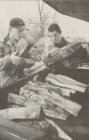 """Andrew Brown and Michael Campbell stack firewood into the back of a truck on Tuesday. They went to the intersection of Delaware Street and Dowlen Road with two pickup loads of firewood and sold out in 15 minutes."" Power lines fell and schools closed during a period of freezing weather in 1997. FIle photo Jan. 15, 1997"