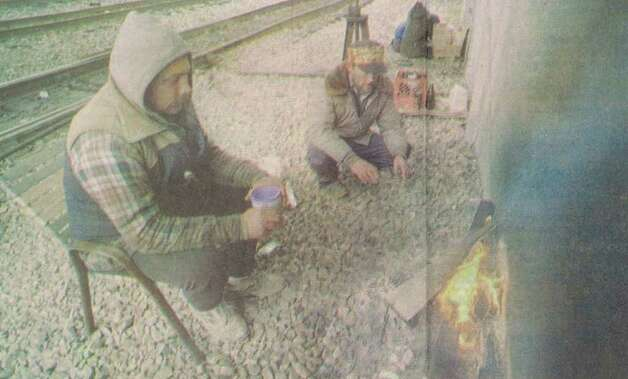 """Eugene Forkum of Virginia, left, and Arthur Wills of New Jersey warm themselves around a small fire Friday afternoon underneath the Hollywood overpass. The pair are passing through Beaumont on their way to San Antonio."" File photo Feb. 3, 1996"