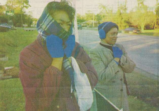 """Cora Garriet and Hinda Briscoe endure the cold as they wait for a bus on 11th Street."" File photo Dec. 19, 1996"