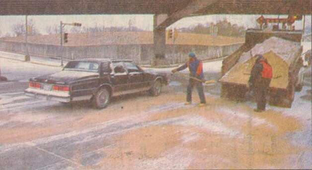 """City workers Alex Bryson, left, and Brenda Conner sand a College Street underpass Friday."" File photo Dec. 23, 1989"