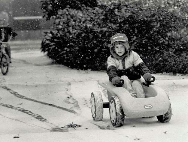 """Seven-year-old Matthew Brown braves record breaking temperatures to take advantage of a rare Southeast Texas snow Friday morning. Matthew and the rest of his family were out enjoying the snow shortly after it started falling this morning."" File photo Dec. 22, 1989"