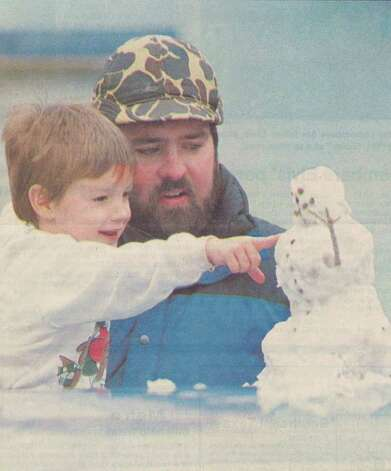 """Casey Dollinger, 3, and his uncle, Willie Miller of Lumberton, make the most of Sunday's snow by making a snowman on Cook's Lake Road near Lumberton."" File photo Feb. 8, 1988"