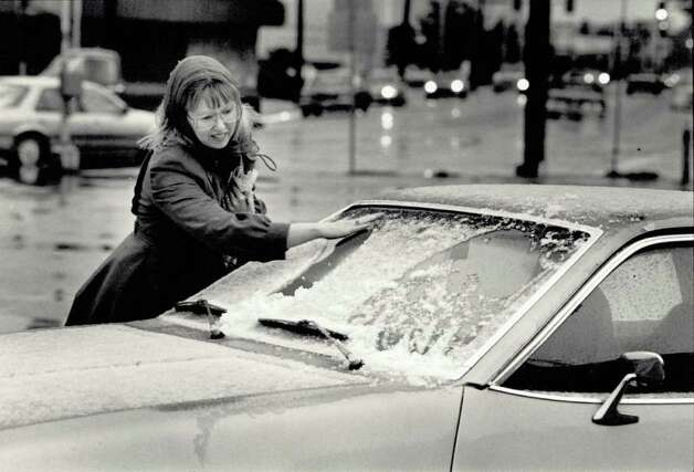 """Sandra Brown of Beaumont brushes away a coating of sleet from her car windshield Friday evening before heading home from work.  She said she had been inside all day and hadn't realized it had gotten cold."" File photo Feb. 5, 1988"