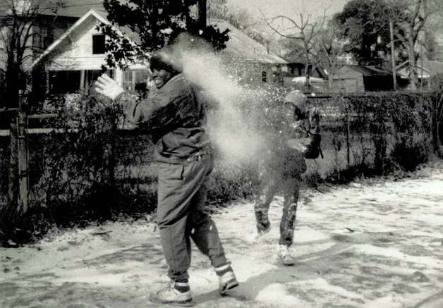 """In the first snow they have ever played in Larry Henry Joseph, 13, and Terrell Henry,9, quickly discover what to do. Said one of the kids playing with them 'We tried to make a snowman but couldn't get him over 1.5 feet tall, so we used him for ammunition instead!'"" Undated file photo"