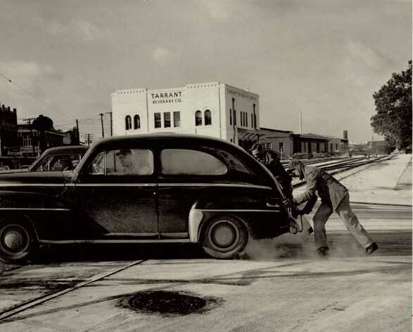 """Automobiles found the going slick at the railroad on Orleans and Crockett. Many a motorist had to resort to hand-propelled help to negotiate the incline."" File photo Feb. 1, 1951"