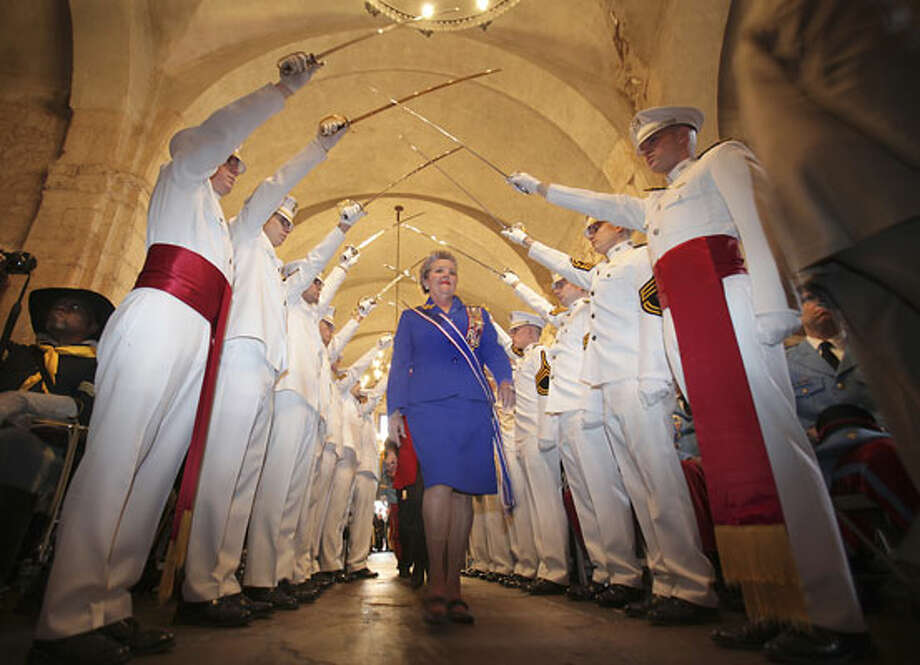 Daughters of the Republic of Texas President General Patti Atkins makes her way under the saber line of the Texas A&M Ross Volunteer Company at the Alamo. Photo: Express-News File