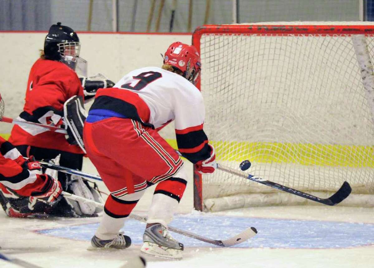 GHS goalie Dart Freccia, left, is helpless as New Canaan High School's Lauren Campbell, # 9, right, converts a blocked rebounded puck into a goal during lst period action of game between Greenwich High School and New Canaan at Darien Rink, Wednesday night, Dec. 8, 2010.