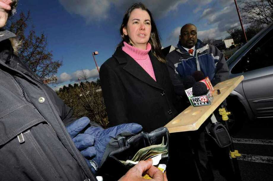 Bobbi Chase Wilding, organizing director of Clean New York, center, reveals findings in a study warning of BPA-tainted sales receipts and money at a Wednesday news conference at the Northway Mall parking lot in Colonie. (Michael P. Farrell/Times Union) Photo: Michael P. Farrell