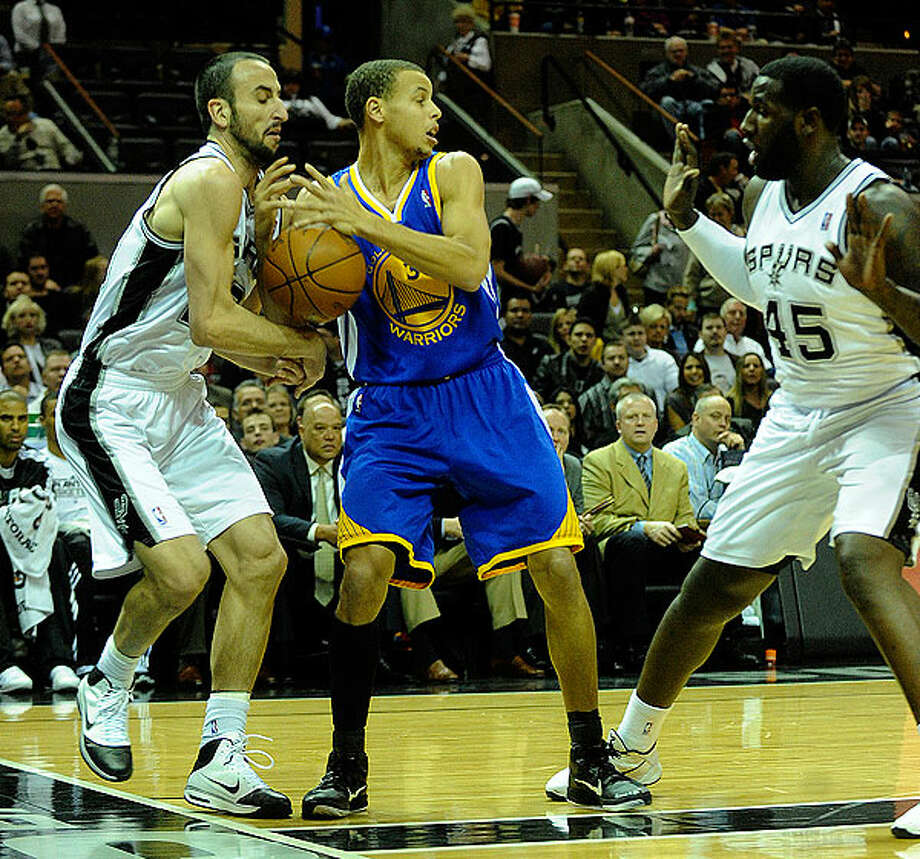 The Spurs' Manu Ginobili (left) and DeJuan Blair defend as the Warriors' Stephen Curry looks to pass during first-half action at the AT&T Center on Wednesday. BILLY CALZADA/gcalzada@express-news.net
