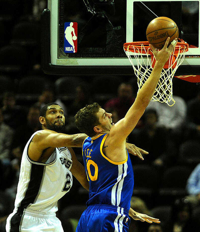 The Warriors' David Lee shoots as the Spurs' Tim Duncan defends during first-half action at the AT&T Center on Wednesday. BILLY CALZADA/gcalzada@express-news.net