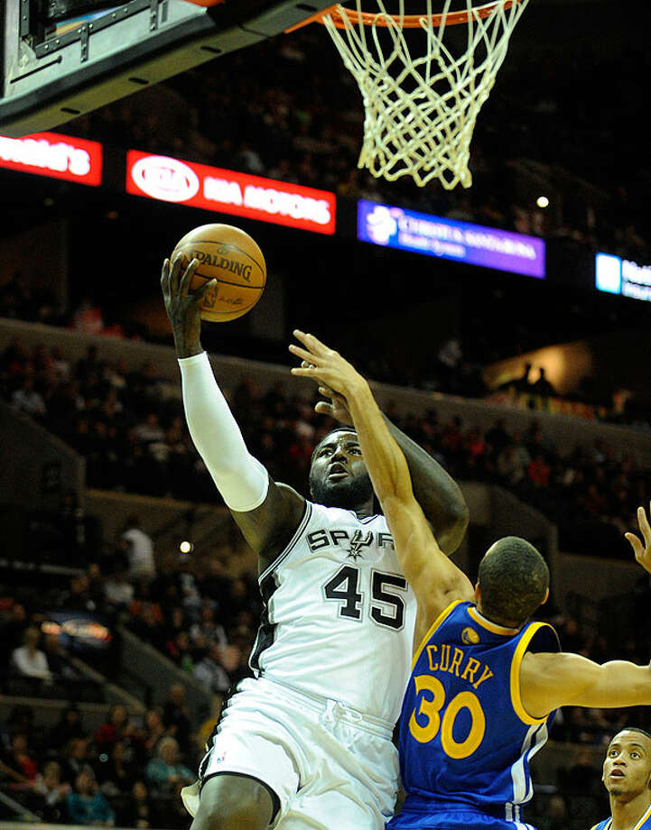 The Spurs' DeJuan Blair shoots a layup as the Warriors' Stephen Curry reaches during first-half action at the AT&T Center on Wednesday. BILLY CALZADA/gcalzada@express-news.net