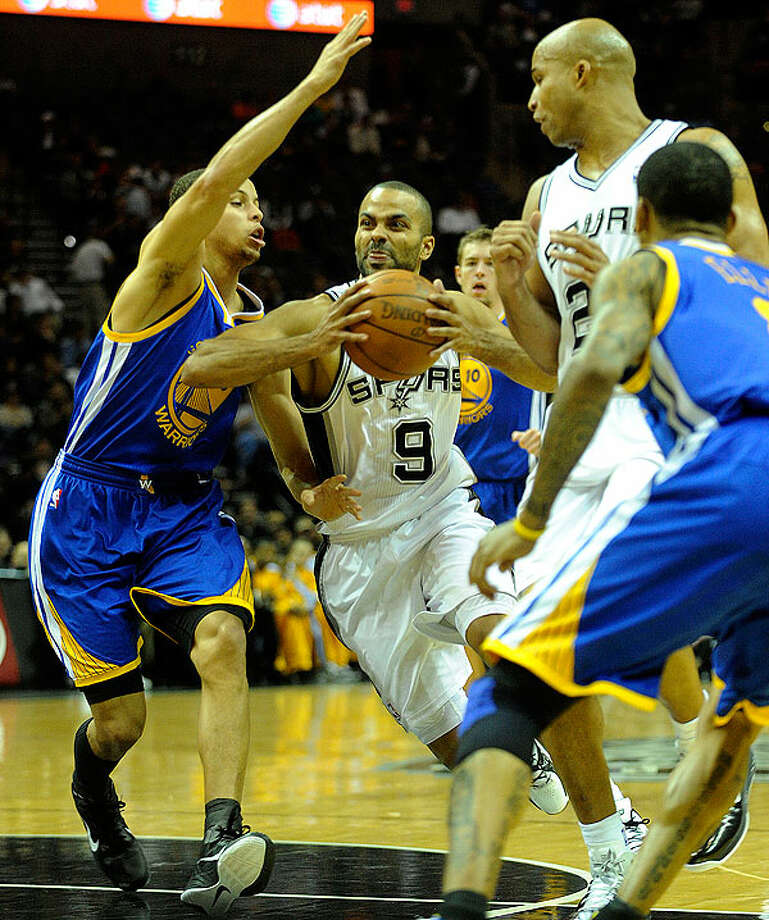 The Spurs' Tony Parker (9) penetrates as the Warriors' Stephen Curry (left) defends during first-half action at the AT&T Center on Wednesday. BILLY CALZADA/gcalzada@express-news.net