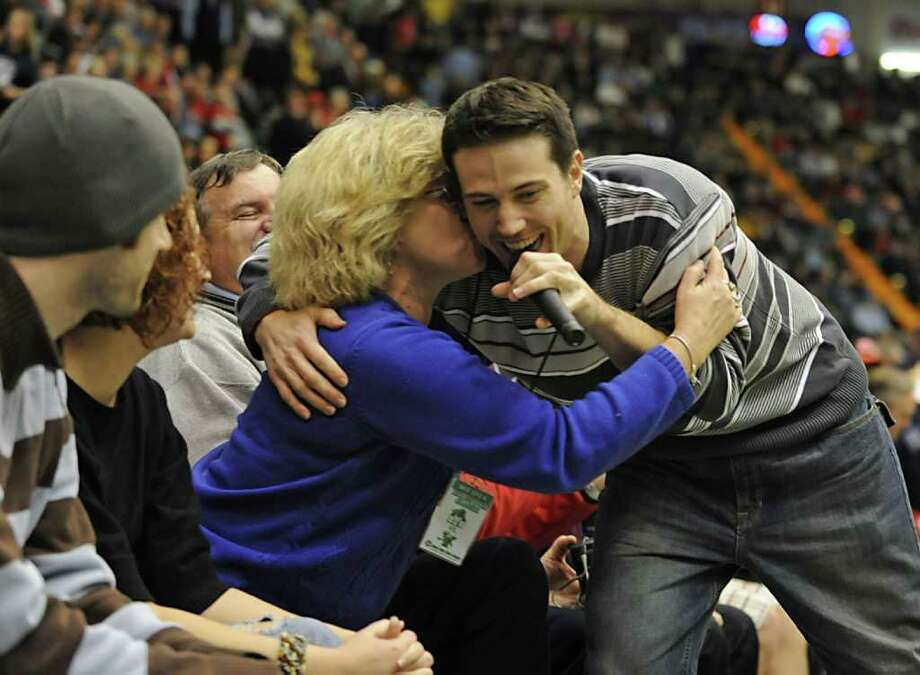 BYU's Jimmer Fredette's brother T.J. Fredette sings a rap song during half time of a basketball game against Vermont and gets a kiss from Bonnie Spencer of Glens Falls. (Lori Van Buren / Times Union) Photo: Lori Van Buren
