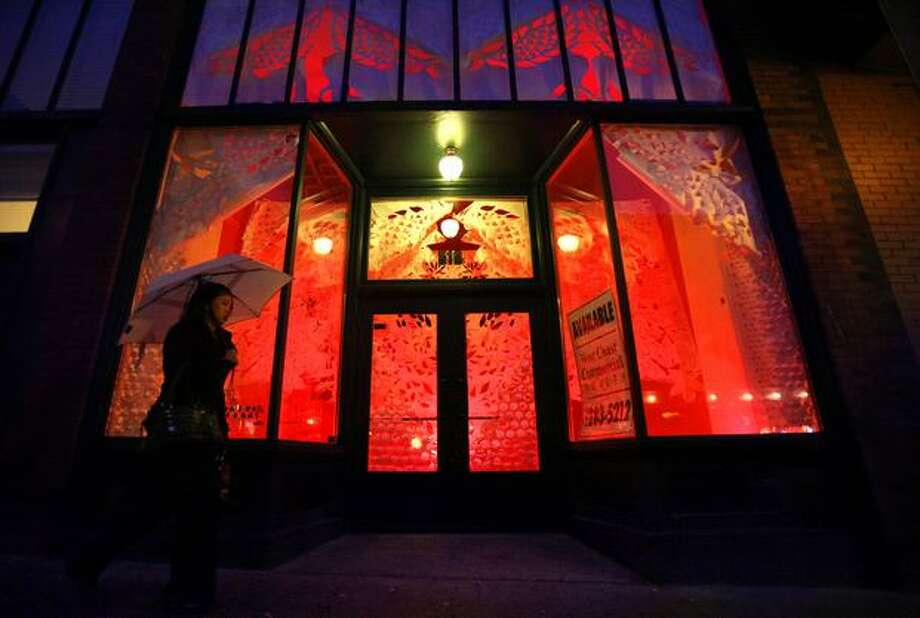 A storefront glows, illuminating paper art in the window of the Eastern Building on Maynard Avenue South in Seattle's International District in this photo taken Wednesday. Photo: Joshua Trujillo/Seattle Post-Intelligencer