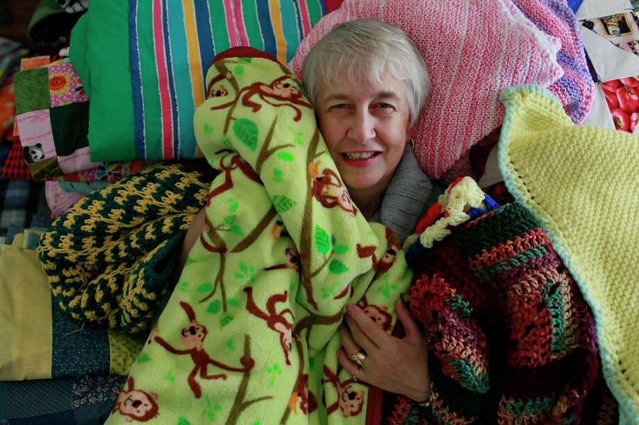 Ann Strautman, coordinator for the San Antonio Chapter of Project Linus, is surrounded by blankets at her home in San Antonio. Photo: LISA KRANTZ/lkrantz@express-news.net / SAN ANTONIO EXPRESS-NEWS