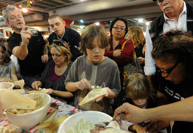 "Jackson Odell (center) and other members of his family prepare tamales during the ""La Gran Tamalada"" event at the Market Square Farmers Market on Saturday, Dec. 4. Photo: Bily Calzada/Express-News"