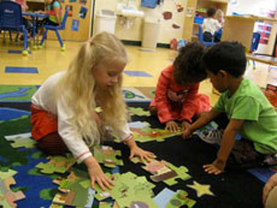 Teyla Bean, 4, (left to right), Eulalia Hinojos, 3, and Andrew Hudson, 4, play with the the Green Start giant floor puzzle, an eco-friendly puzzle that matches a wild animal with each letter of the alphabet. The puzzle also teaches spatial relationships and sorting. Photo by Kelly Chapman Lozano