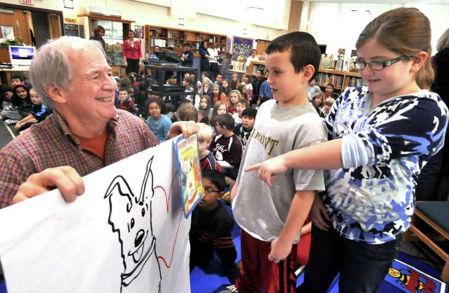 Steven Kellogg, author and illustrator, shows Pinkerton, one of his characters, to Kamren Kresmery and Alexandra Luhrs, third-graders at Berry School in Bethel, Thursday, Dec. 9, 2010. Photo: Michael Duffy / The News-Times