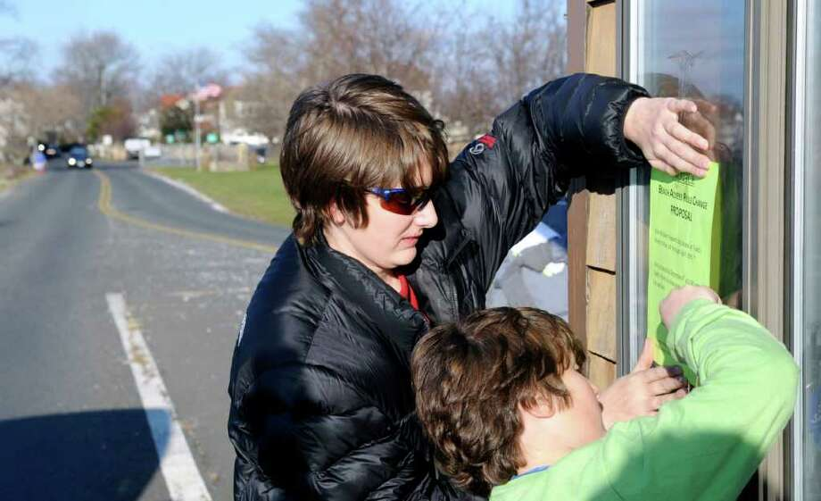 Spencer Grabel, 11, left, of Greenwich, gets help from his brother, Michael, 9, as the pair post a notice of protest on the guard booth at Greenwich Point, Thursday, Dec. 2, 2010. Spencer organized a protest for Saturday, Dec. 4, at Greenwich Point over the town's current canine-access policy at Greenwich Point, which limits dogs to four months, December through March. Photo: File Photo / Greenwich Time File Photo
