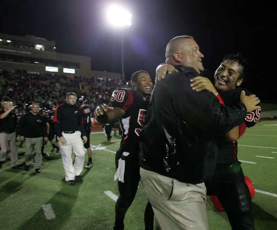 Coldspring head coach Bryan Barbay celebrates the Trojans' 44-14 victory over Athens with players Cameron Carrier (50) and CJ Duenas, Friday at Bowers Stadium in Huntsville. Photo: ERIC CHRISTIAN SMITH, FOR THE CHRONICLE / Beaumont