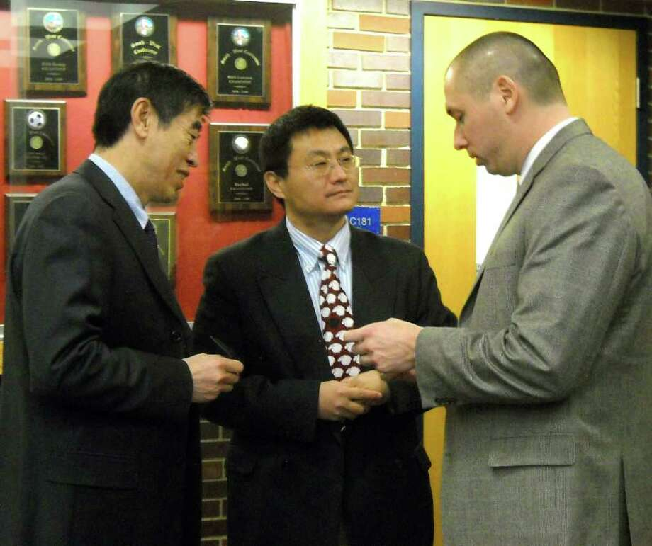 Newtown High School Assistant Principal Jason Hiruo accepts business cards from delegates of the Chinese Ministry of Education, who visited Newtown High School Thursday, Dec. 9, 2010. Photo: Stacy Davis / The News-Times