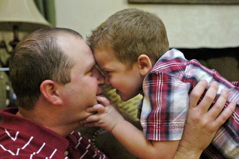 """Three year old Dawson Brown, right, """"attacks"""" his father Cory Brown during a little wrestling match Thursday afternoon. Dawson was diagnosed with Acute Lymphoblastic Leukemia last year. His family has had to drive weekly from Beaumont to Houston's Texas Children's Cancer Center for a year long course of antibiotics in addition to a regimen of steroids. He still has two more years of treatments to go.   Dave Ryan/The Enterprise Photo: Dave Ryan / Beaumont"""