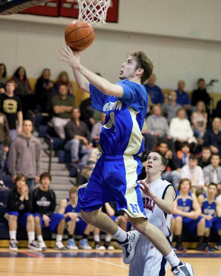 Newtown's Josh Engler scores on a fastbreak layup after getting past New Fairfield defender Joe Silva during their SWC game Wednesday night at New Fairfield High. Photo: Barry Horn / The News-Times Freelance