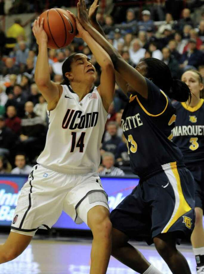 Connecticut's Bria Hartley, left, comes in for a shot as Marquette's Tatiyana McMorris tries to guard her in the first half of an NCAA college basketball game at Storrs, Conn., Thursday, Dec. 9, 2010. (AP Photo/Bob Child) Photo: AP