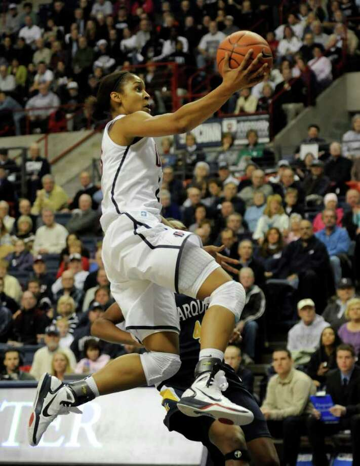 Connecticut's Maya Moore, top, jumps past Marquette's Paige Fiedorowicz for a shot in the first half of an NCAA college basketball game at Storrs, Conn., Thursday, Dec. 9, 2010. (AP Photo/Bob Child) Photo: AP
