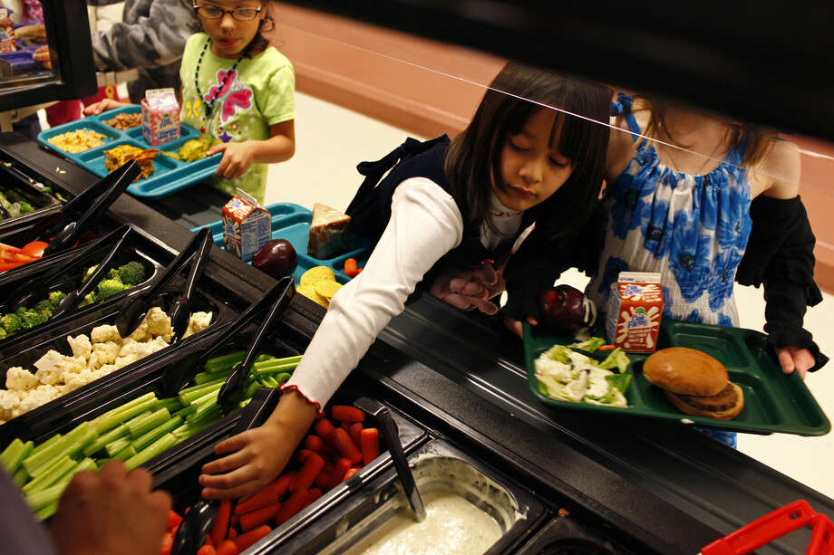Haley Trevino (left) ponders her choices as Elle Littlebird helps herself to veggies at Cambridge Elementary in Alamo Heights, which is ahead of the curve on salad bars. Photo: LISA KRANTZ/lkrantz@express-news.net