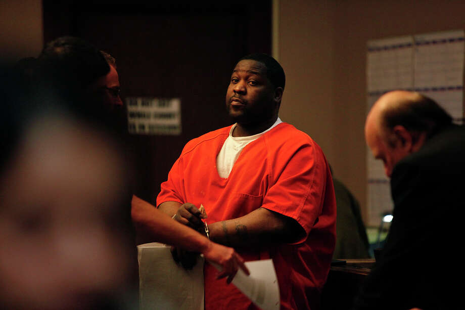 Donald Evans is processed after being sentenced to 25 years in prision in connection with the murder of Ernest Davilla. Evans says he was outside in the car during the shooting. Photo: LISA KRANTZ/lkrantz@express-news.net