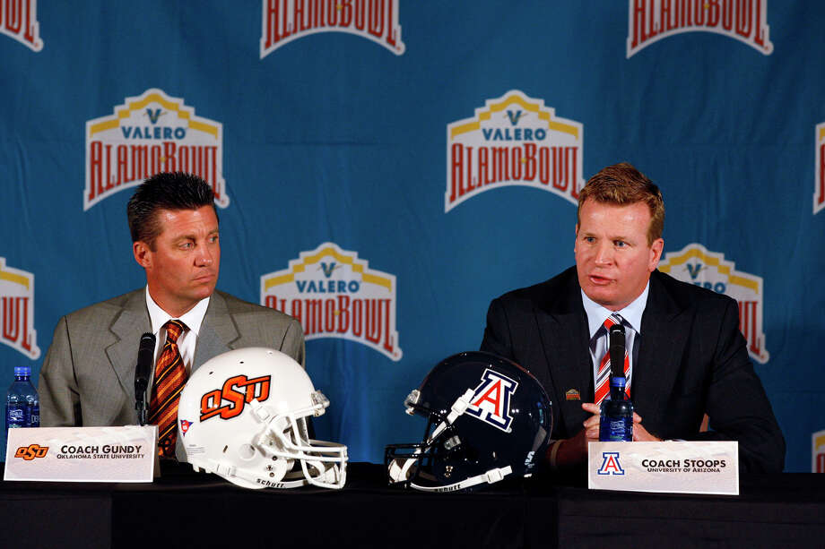 Arizona coach Mike Stoops (right) and Oklahoma State coach Mike Gundy discuss their meeting in the Dec. 29 Alamo Bowl on Thursday. Photo: JERRY LARA/glara@express-news.net