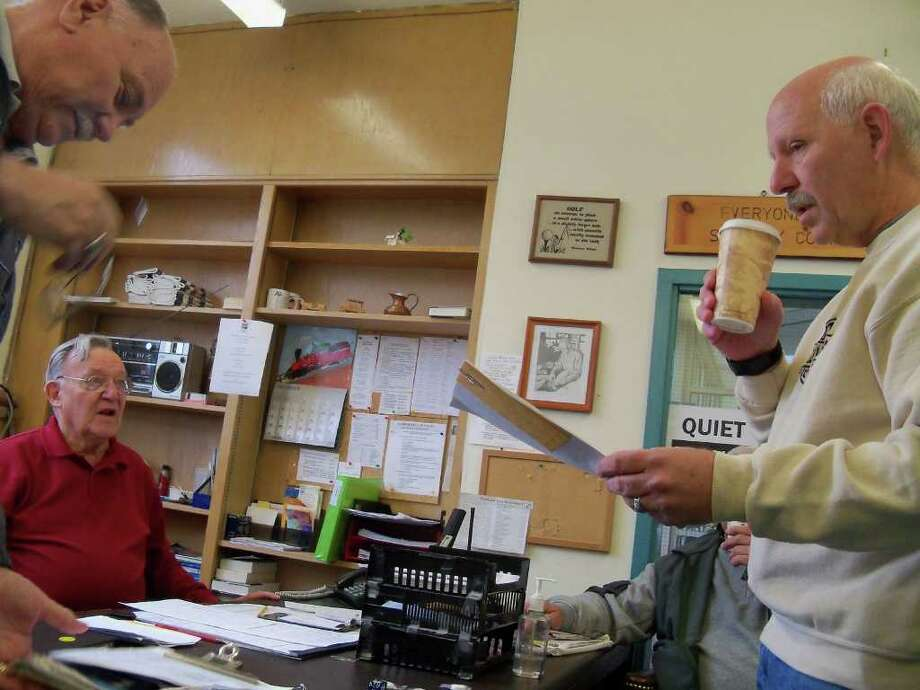 Retired Police Chief David Peck, right, goes over the list for his morning bus route for the Senior Center with Hank Steffans, seated, and Denes Fazekas. Peck has been a part-time driver for the center since August. Photo: Genevieve Reilly / Fairfield Citizen