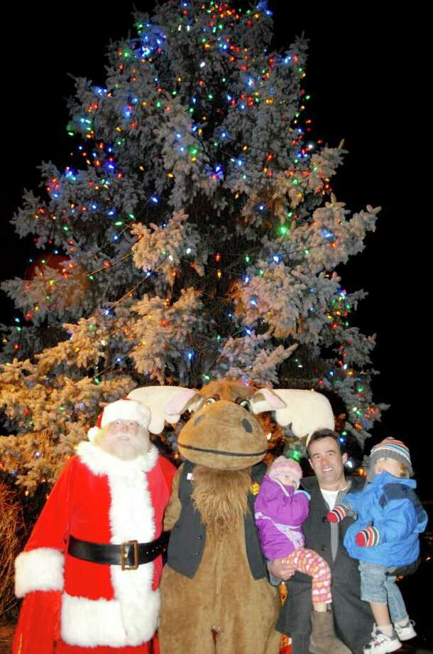 Santa and a reindeer pose with John Phillips and his children Lindsey and Dylan at the Upper Union Street Business Improvement District's tree lighting ceremony in Schenectady. (Luanne M. Ferris / Times Union ) Photo: Luanne M. Ferris