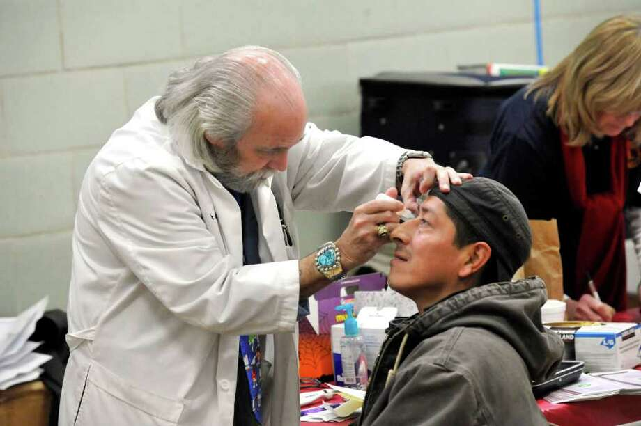 Dr. Joseph Young examines Angelo Zuniga's eye pressure for glaucoma at the Danbury Lions Club area during Danbury Project Homeless Connect at Western Connecticut State University's midtown campus, Friday, Dec. 10, 2010. Photo: Michael Duffy / The News-Times
