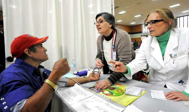 Maria Fernandes, center, and Alice Correia, of Danbury Hospital's Seifert and Ford Family Health Center, check Luis Pomauilla's blood pressure during Danbury Project Homeless Connect at Western Connecticut State University's midtown campus, Friday, Dec. 10, 2010. Photo: Michael Duffy / The News-Times