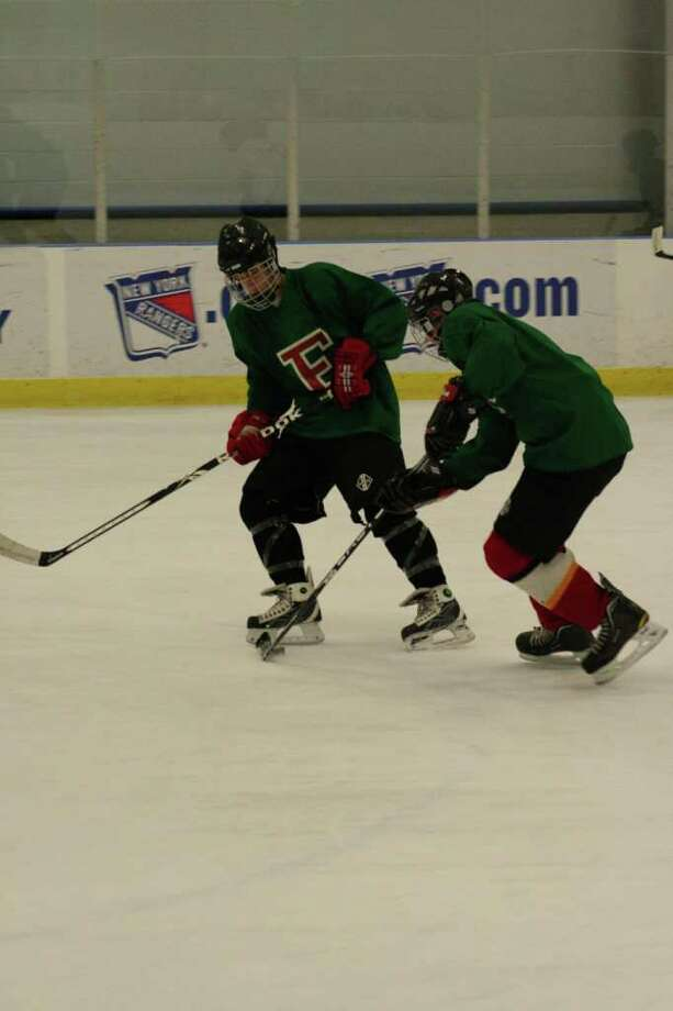 Fairfield captain Chris Santello works with sophomore linemate Tom Crispin during a drill in practice at Wonderland of Ice. Photo: Tim Parry / Fairfield Citizen freelance