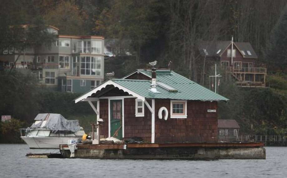 A house barge floats in Bainbridge Island's Eagle Harbor on Wednesday, November 17, 2010. Boat owners and the liveaboard community were served eviction notices by the Washington State Department of Natural Resources this week after plans with the Bainbridge City Council for an open-water marina were scrapped. For decades the harbor has hosted the community made up of an assortment of boats and house barges. The floating homes were moored on the state-managed sea floor free of charge. (Joshua Trujillo, Seattlepi.com). Photo: Joshua Trujillo/seattlepi.com