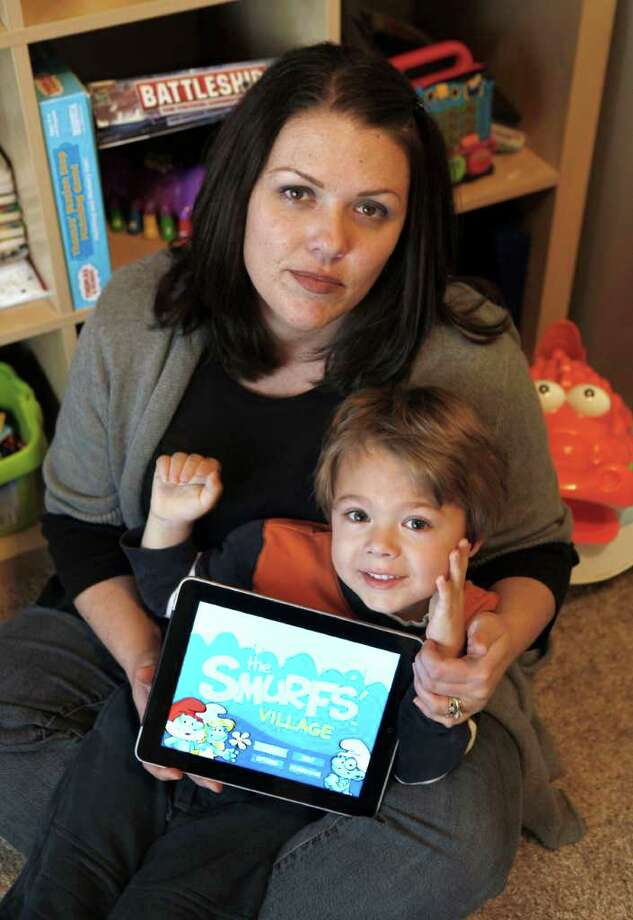 """In this photo taken Dec. 7, 2010,  Kelly  Rummelhart and her son, Sawyer, 4, who unwittingly racked up nearly $70 in purchases on """"The Smurf's Village"""" game he played on her IPad, are seen in their home in Gridley, Calif.(AP Photo/Rich Pedroncelli) Photo: Rich Pedroncelli, STF / AP"""