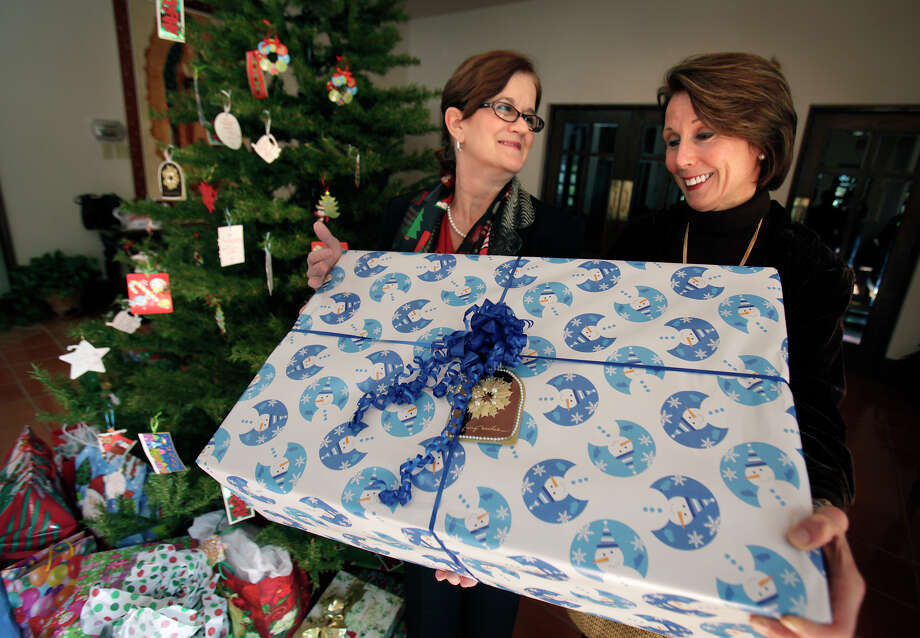 Paula Walker, director of refugee services at Catholic Charities (left), and Becky Finley, business manager for St. Peter Prince of the Apostles Catholic Church, hold a present destined for members of a refugee family in front of the Giving Tree at the church. Photo: Bob Owen/rowen@express-news.net / SAN ANTONIO EXPRESS-NEWS