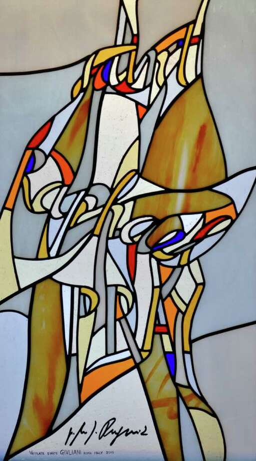 "Each of the stained glass windows at the Chapel of the Holy Spirit, on the campus of Sacred Heart University in Fairfield, features a modernist design with splashes of color in which words (rather than images) are interwoven referencing the people and events in the story of salvation.  This ""Saint Raphael Pray for us"" window is signed by he artist, the Rev. Marko Rupnik of Rome. Photo: CONTRIBUTED PHOTO"