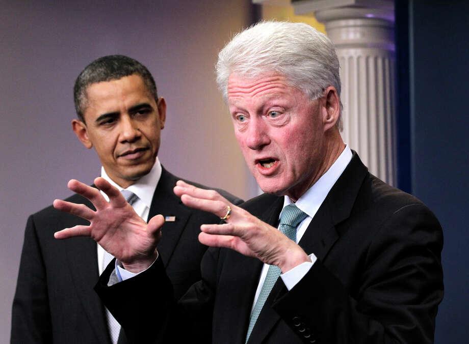 President Barack Obama looks on as former President Bill Clinton speaks in the briefing room of the White House in Washington on Friday. Photo: J. Scott Applewhite/Associated Press