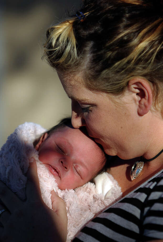 Amber Gann-Cisneros, a victim of domestic violence who this summer would have gone to a shelter in Boerne if one existed, holds her infant daughter Katarina. Photo: Kin Man Hui/kmhui@express-news.net