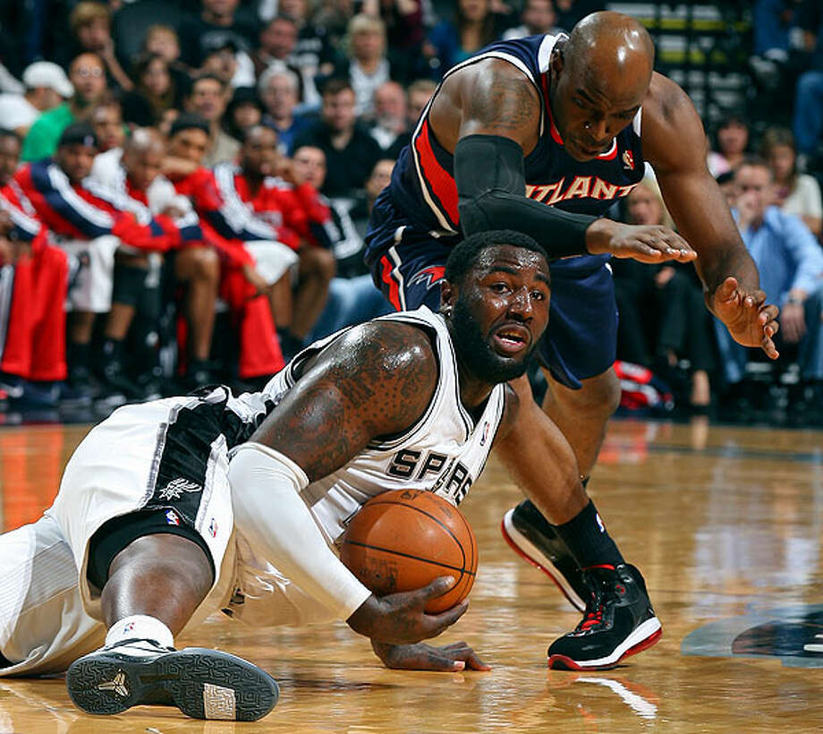 The Spurs' DeJuan Blair grabs for a loose ball under the Hawks' Damien Wilkins during first-half action Friday, Dec. 10, 2010 at the AT&T Center. (PHOTO BY EDWARD A. ORNELAS/eaornelas@express-news.net)