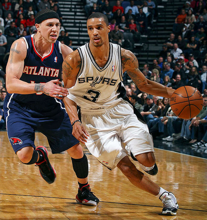 The Spurs' George Hill drives around the Hawks' Mike Bibby during first-half action Friday, Dec. 10, 2010 at the AT&T Center. (PHOTO BY EDWARD A. ORNELAS/eaornelas@express-news.net)