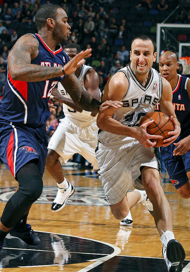 The Spurs' Manu Ginobili looks for room around the Hawks' Josh Powell during first-half action Friday, Dec. 10, 2010 at the AT&T Center. (PHOTO BY EDWARD A. ORNELAS/eaornelas@express-news.net)