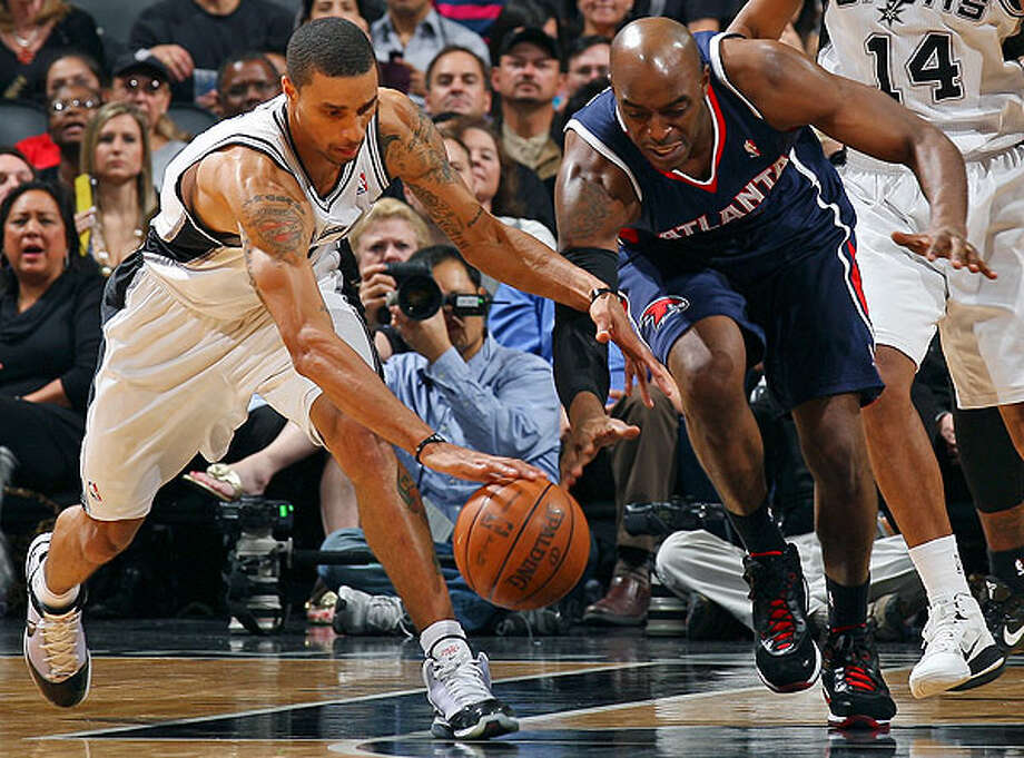 The Spurs' George Hill and Hawks' Damien Wilkins grab for a loose ball during second-half action Friday, Dec. 10, 2010 at the AT&T Center. The Spurs won 108-92. (PHOTO BY EDWARD A. ORNELAS/eaornelas@express-news.net)