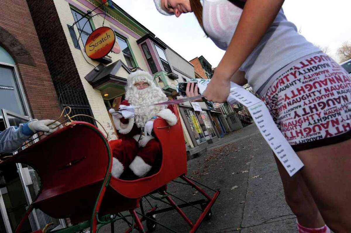 Mike Houghton playing Santa goes over his naughty and nice list with Lisa Hlebica of Albany before the start of the fifth annual Santa Speedo Sprint in Conjunction with the fourth annual Winter WonderLark in Albany on Saturday, Dec. 11. ( Michael P. Farrell/Times Union )