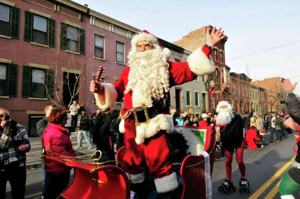 Mike Houghton, playing Santa, waves from his people-powered sled as he heads to the finish of the Santa Speedo Sprint on Saturday, Dec. 11. ( Michael P. Farrell/Times Union )